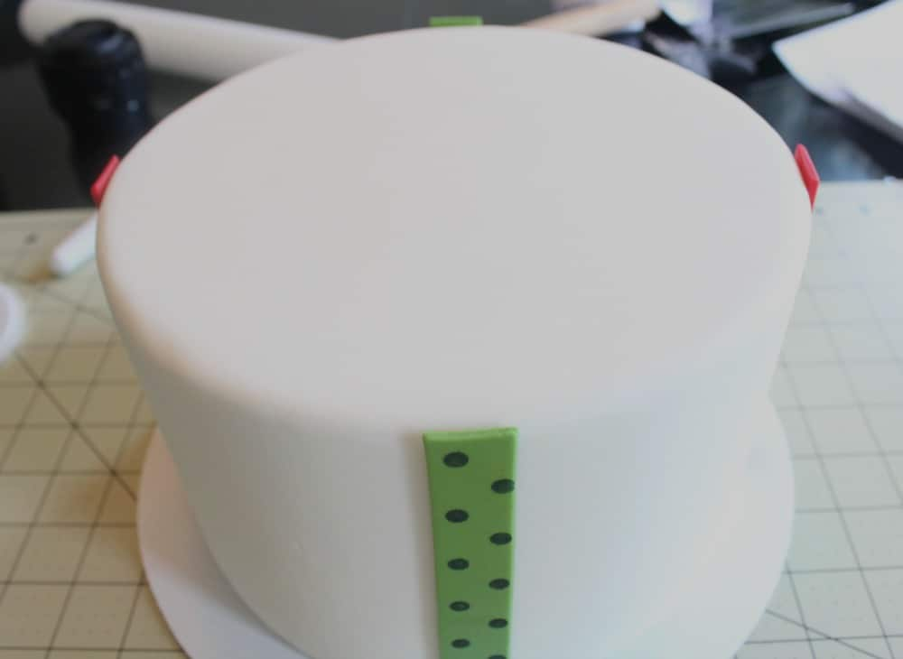 attaching second strip of fondant to cake